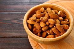 Raw dry nuts of almonds in a wooden bowl on a wooden table. Raw dry nuts of almonds in a wooden bowl on a wooden table Stock Photo