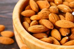 Raw dry nuts of almonds in a wooden bowl on a wooden table. Raw dry nuts of almonds in a wooden bowl on a wooden table Royalty Free Stock Images