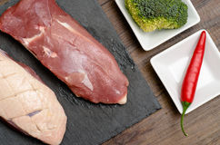 Raw duck breast with chili pepper and broccoli Stock Photo