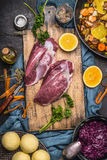 Raw Duck breast with ingredients for tasty cooking: oranges,vegetables,  dumpling and red cabbage on cutting board at dark rustic Stock Photos