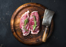 Raw duck breast with rosemary and cleaver on wooden tray. Raw uncooked poultry meat cut. Duck breast with rosemary and butcher cleaver on dark wooden tray over Stock Photography