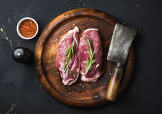 Raw duck breast with rosemary, spices on dark wooden tray Royalty Free Stock Images