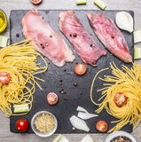 Raw duck breast with spaghetti, cherry tomatoes, black pepper, chopped onions other seasonings, laid out on the marble rustic Royalty Free Stock Photos