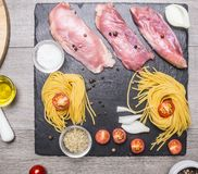 Raw duck breast with spaghetti, cherry tomatoes, black pepper, chopped onions  other seasonings, laid out on the marble rustic Royalty Free Stock Photography