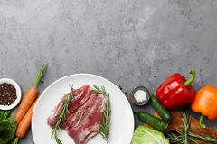 Raw duck breast in white plate with vegetables. Raw duck breast, fresh vegetables, herbs and spices on gray stone background, copyspace Stock Photography