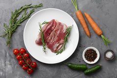 Raw duck breast in white plate with vegetables. Raw duck breast, fresh vegetables, herbs and spices on gray stone background, top view Stock Photography