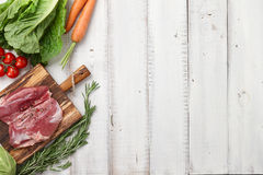 Raw duck breast in white plate and vegetables. Raw duck breast in plate and fresh vegetables on white wooden background Royalty Free Stock Images
