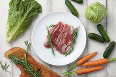 Raw duck breast in white plate and vegetables. Raw duck breast in plate and fresh vegetables on white wooden background Royalty Free Stock Photo