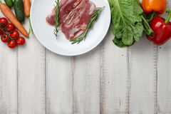 Raw duck breast in white plate and vegetables. Raw duck breast in plate and fresh vegetables on white wooden background Stock Photo