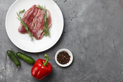 Raw duck breast in white plate with vegetables. On gray stone background Stock Images