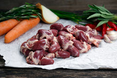 Raw Duck hearts on crumpled paper, decorated with greens and vegetables. on old  wooden table Stock Photos