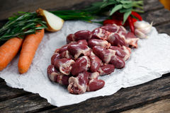 Raw Duck hearts on crumpled paper, decorated with vegetables. on. Old wooden table Stock Image