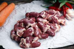Raw Duck hearts on crumpled paper, decorated with vegetables. On old wooden table Royalty Free Stock Image