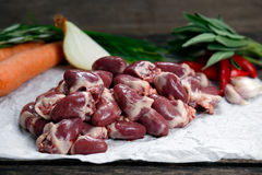 Raw Duck hearts on crumpled paper, decorated with vegetables. On old wooden table Royalty Free Stock Images