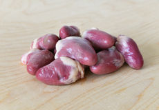 Raw duck hearts. Duck offal - raw hearts on a wooden cutting board Royalty Free Stock Photography