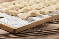 Raw dumplings on wooden cutting board, is ready to boil. Also known as Vareniks. Ukrainian traditional cuisine. Raw dumplings on wooden cutting board, ready to stock images