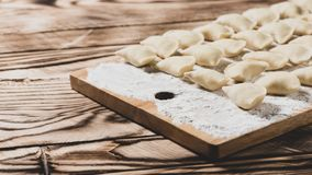 Raw dumplings on wooden cutting board, is ready to boil. Also known as Vareniks. Ukrainian traditional cuisine. Matte effect. Raw dumplings on wooden cutting royalty free stock photography