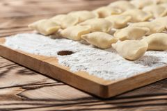 Raw dumplings on wooden cutting board, is ready to boil. Also known as Vareniks. Ukrainian traditional cuisine. Raw dumplings on wooden cutting board, ready to stock photo
