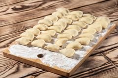 Raw dumplings on wooden cutting board, is ready to boil. Also known as Vareniks. Ukrainian traditional cuisine. Raw dumplings on wooden cutting board, is ready royalty free stock photography