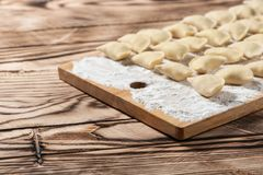 Raw dumplings on wooden cutting board, is ready to boil. Also known as Vareniks. Ukrainian traditional cuisine. Raw dumplings on wooden cutting board, ready to stock photography