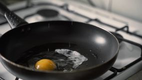 Raw egg is falling into hot pan in slow motion and roasting stock footage