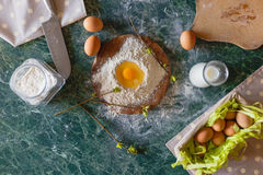 Raw egg in a handful of flour. Spring pie cooking. Top view. Stock Image