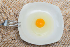 Raw egg on a white plate Royalty Free Stock Photo