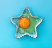 Raw egg yolk small decorative star-shaped bowl Royalty Free Stock Photo