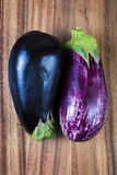 Raw eggplants over wood background Royalty Free Stock Images