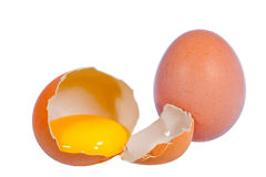 Raw eggs. Close up on two raw eggs, one broken, one whole isolated on white background Stock Image