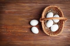 Raw eggs in basket. On wooden background Stock Photo