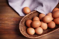 Raw eggs in basket. On wooden background Stock Photos