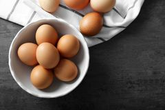 Raw eggs in bowl. On kitchen table Stock Photo