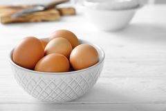 Raw eggs in bowl. On kitchen table Royalty Free Stock Images