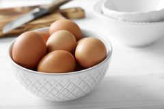 Raw eggs in bowl. On kitchen table Stock Photography