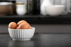 Raw eggs in bowl on   table. Raw eggs in bowl on kitchen table Stock Photo