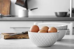 Raw eggs in bowl on   table. Raw eggs in bowl on kitchen table Stock Images