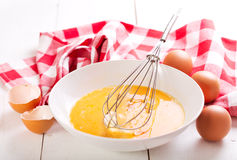 Raw eggs in bowl. Raw eggs with whisk in bowl on wooden table Stock Photo
