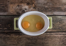 Raw eggs in the bowl. Raw eggs on wood board table Stock Image