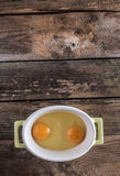 Raw eggs in the bowl. On wooden board Royalty Free Stock Photography