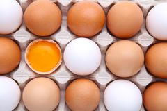 Raw eggs in carton for background. Chicken egg is half broken among other eggs royalty free stock photography