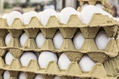 Raw eggs in carton displays for sale in a food market. Raw white eggs in carton displays for sale in a food market Royalty Free Stock Image