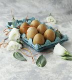 Raw eggs in a carton for eggs with white flowers on a marble white table, ready for painting Easter, selective focus. Raw eggs in a carton for eggs with white Royalty Free Stock Photography