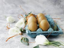 Raw eggs in a carton for eggs with white flowers on a marble white table, ready for painting Easter, selective focus. Raw eggs in a carton for eggs with white Royalty Free Stock Photos