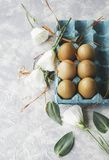 Raw eggs in a carton for eggs with white flowers on a marble white table, ready for painting Easter, selective focus. Raw eggs in a carton for eggs with white Stock Photo