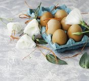Raw eggs in a carton for eggs with white flowers on a marble white table, ready for painting Easter, selective focus. Raw eggs in a carton for eggs with white Stock Photos