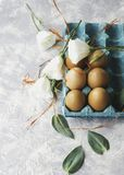 Raw eggs in a carton for eggs with white flowers on a marble white table, ready for painting Easter, selective focus. Raw eggs in a carton for eggs with white Stock Images
