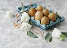 Raw eggs in a carton for eggs with white flowers on a marble white table, ready for painting Easter, selective focus. Raw eggs in a carton for eggs with white Stock Image