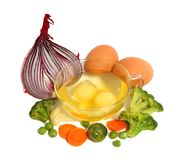 Raw eggs and different vegetables. Raw eggs in a glass cup and different vegetables, healthy breakfast Stock Photo
