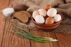 Raw eggs in an earthenware bowl, onions, bread, salt shaker Royalty Free Stock Image